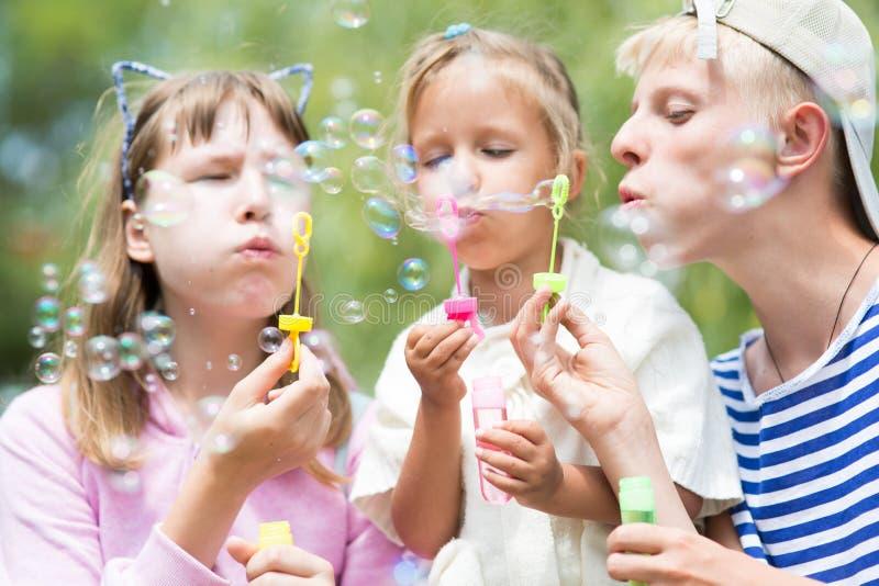 Crianças que fundem bolhas de sabão imagem de stock royalty free