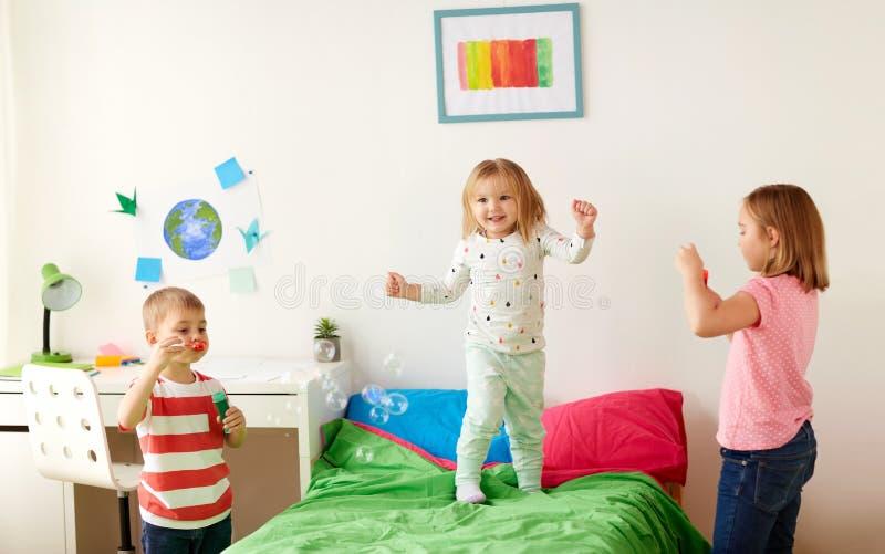 Crianças que fundem bolhas de sabão e que jogam em casa imagem de stock