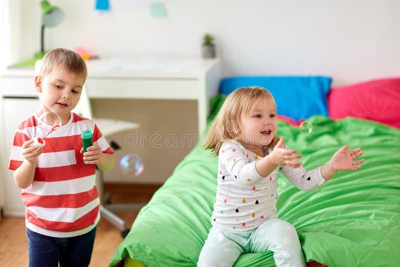 Crianças que fundem bolhas de sabão e que jogam em casa foto de stock royalty free