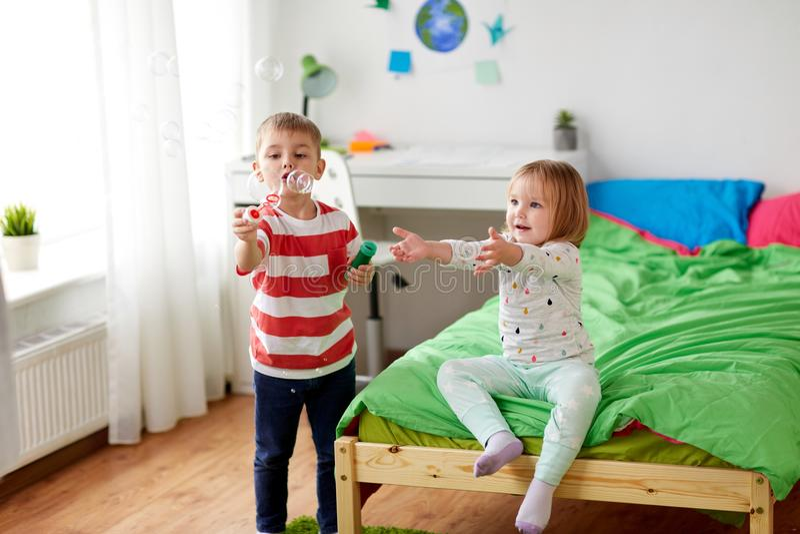 Crianças que fundem bolhas de sabão e que jogam em casa imagens de stock