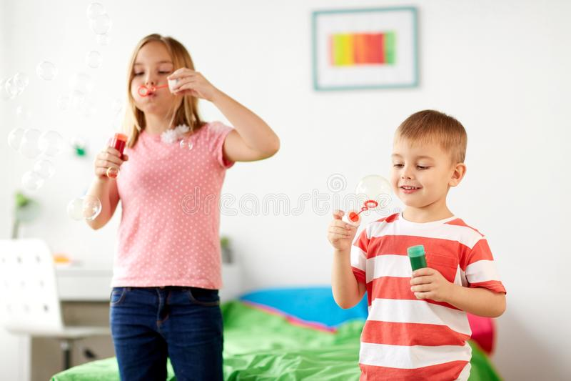 Crianças que fundem bolhas de sabão e que jogam em casa fotos de stock royalty free