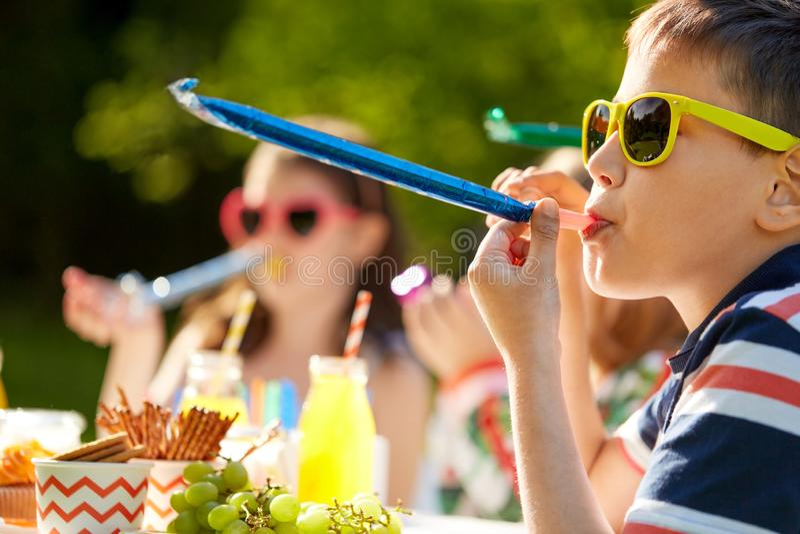 Crianças que fundem chifres do partido no aniversário no verão fotos de stock