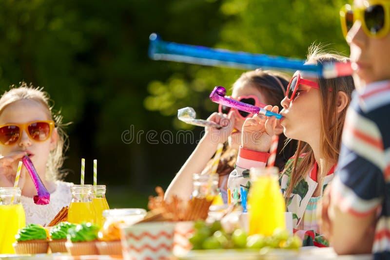Crianças que fundem chifres do partido no aniversário no verão foto de stock royalty free