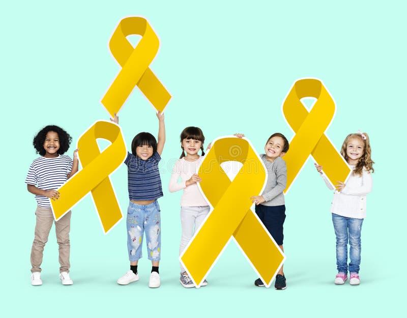 Crianças que guardam as fitas do ouro que apoiam a conscientização do câncer da infância imagem de stock