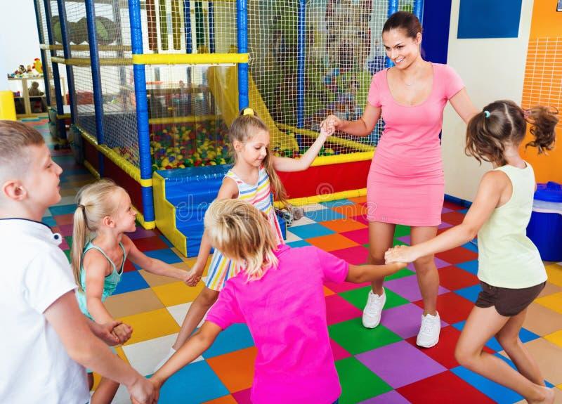 Crianças que guardam cada outro mãos e que dançam com professor fotografia de stock royalty free