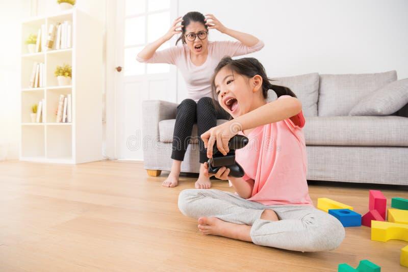 Crianças que guardam o controlador que joga jogos de vídeo fotografia de stock
