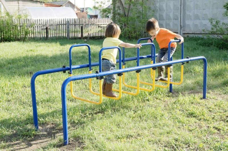 Crianças que jogam ao ar livre Menino e menina no campo de jogos, atividade das crianças Infância saudável ativa fotos de stock