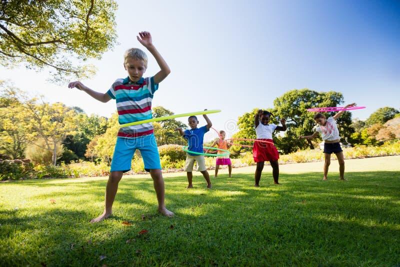 Crianças que jogam a aro junto durante um dia ensolarado imagem de stock