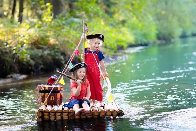 Crianças que jogam a aventura do pirata na jangada de madeira imagens de stock