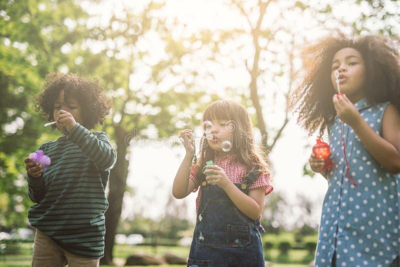 Crianças que jogam bolhas de sopro junto no campo fotos de stock