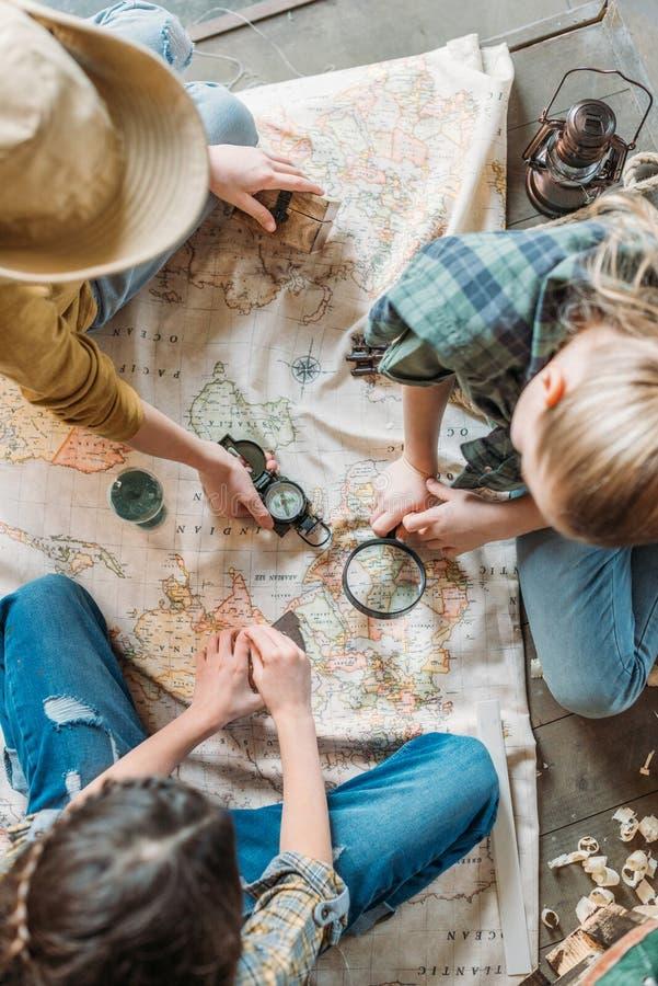 Crianças que jogam a caça ao tesouro com o mapa no patamar imagem de stock