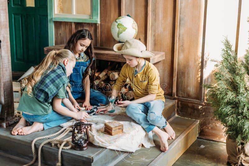 Crianças que jogam a caça ao tesouro com o mapa no patamar fotografia de stock