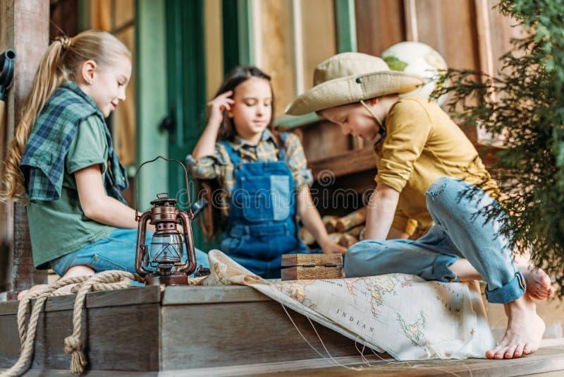 Crianças que jogam a caça ao tesouro com o mapa no patamar foto de stock
