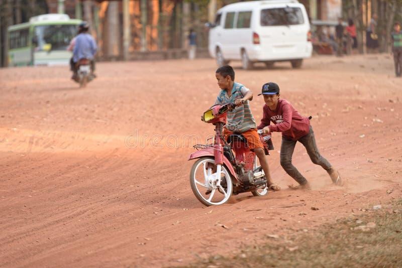 Crianças que jogam com bicicleta motorizada fotografia de stock