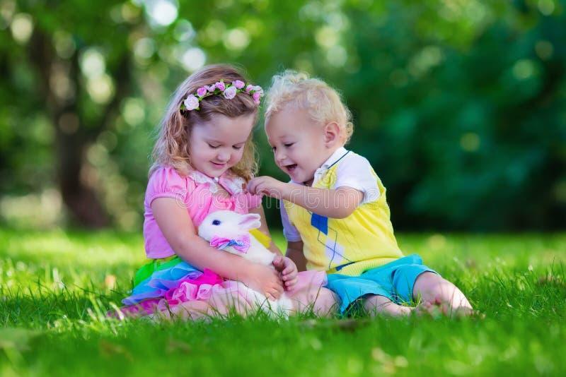 Crianças que jogam com coelho do animal de estimação foto de stock royalty free