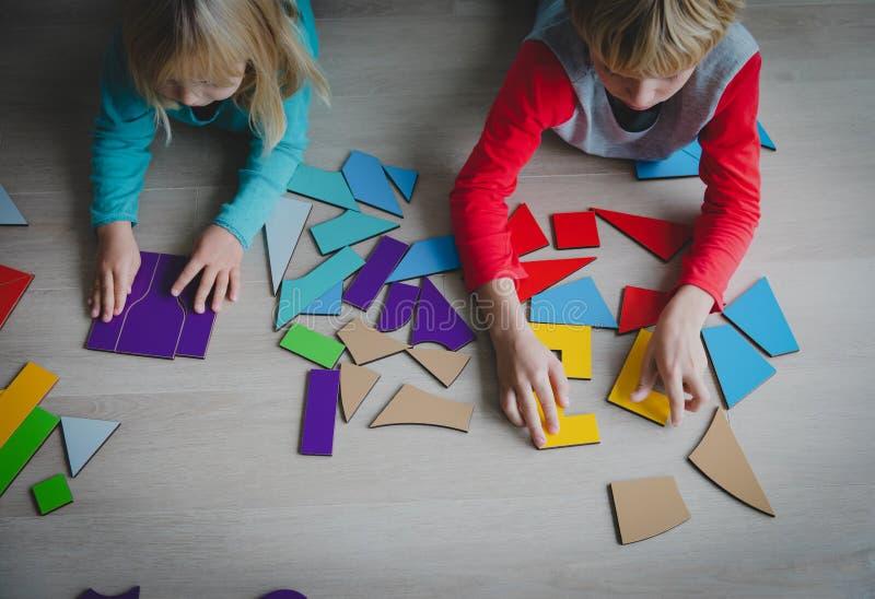 Crianças que jogam com enigma ou tangram, conceito da educação fotos de stock