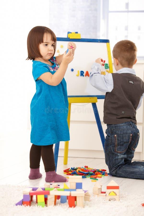 Crianças que jogam com mesa de projecto foto de stock royalty free