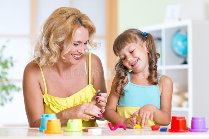 Crianças que jogam com moldar colorido da argila diferente foto de stock royalty free