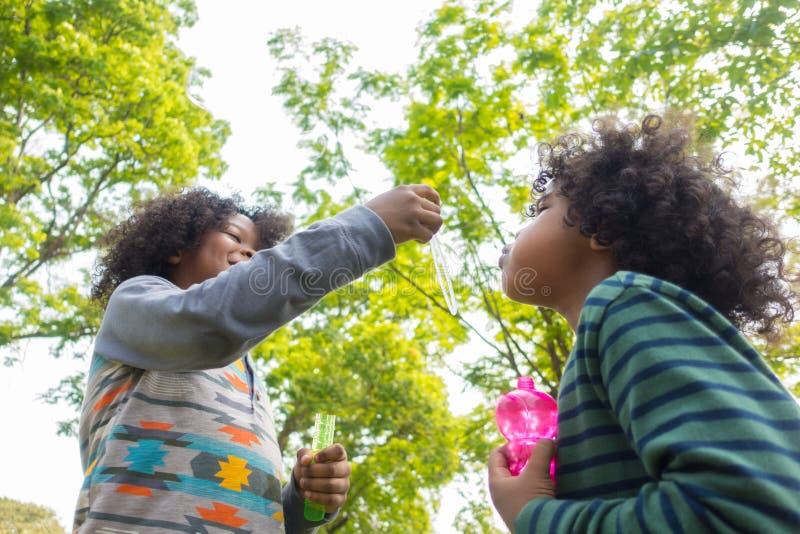 Crianças que jogam com os amigos que fundem bolhas imagens de stock royalty free
