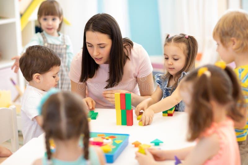 Crianças que jogam com os brinquedos educacionais no jardim de infância Professor do berçário que ocupa de crianças imagens de stock