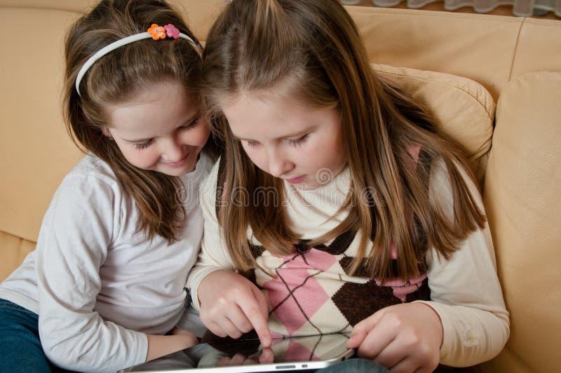 Crianças que jogam com tabuleta foto de stock