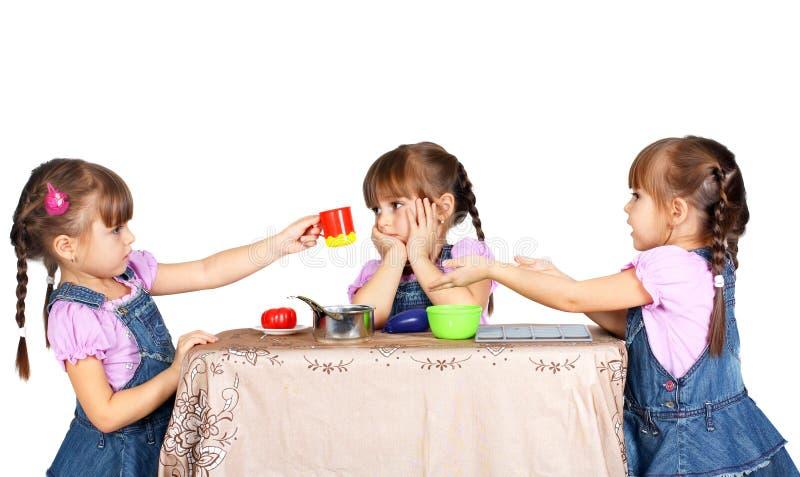 Crianças que jogam com utensílios de mesa plásticos fotografia de stock