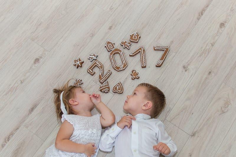 Crianças que jogam com véspera do ` s do ano novo do pão-de-espécie imagens de stock