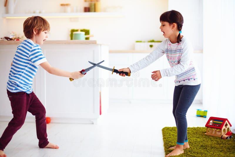 Crianças que jogam a cozinha ativa dos jogos da luta em casa imagens de stock