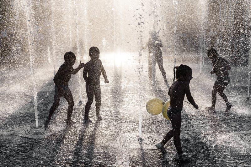Crianças que jogam em uma fonte fotografia de stock royalty free