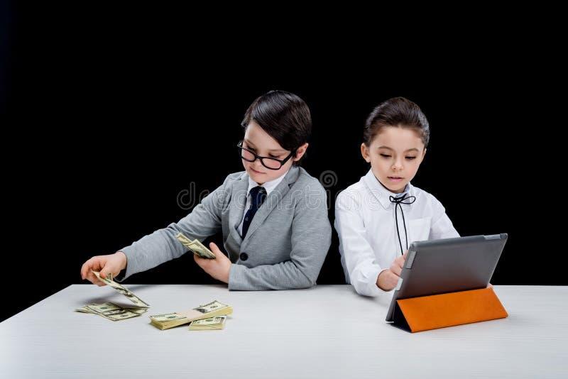 Crianças que jogam executivos com dinheiro e portátil foto de stock