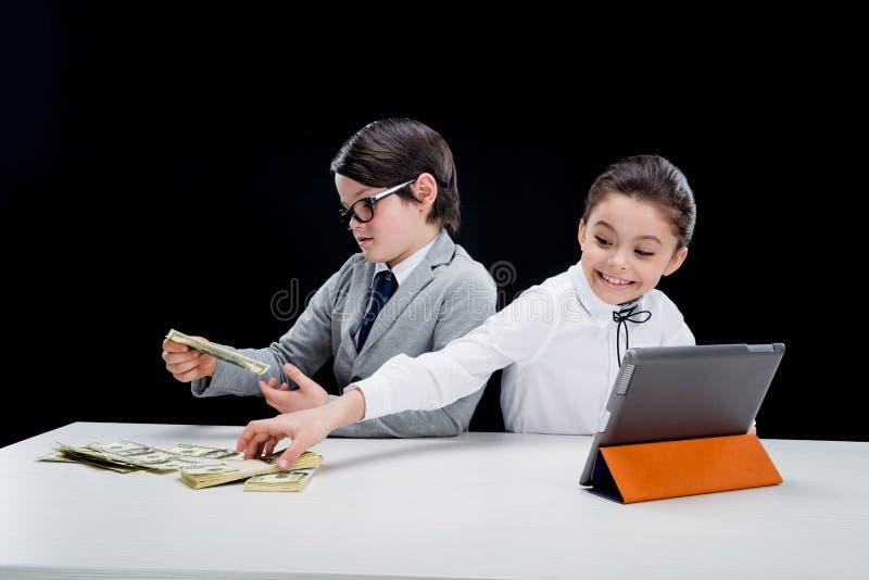 Crianças que jogam executivos com dinheiro e tabuleta fotos de stock royalty free