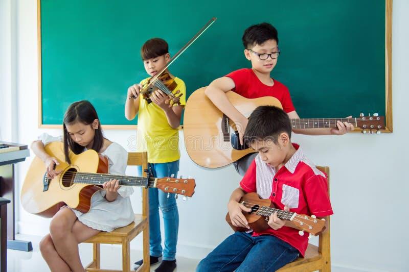 Crianças que jogam instrumentos de música na sala de aula da música imagem de stock