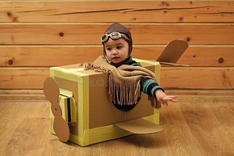 Crianças que jogam - jogo feliz Menino bonito pequeno que joga com um avião do cartão foto de stock