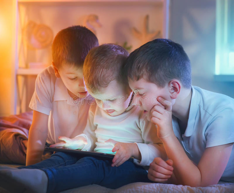 Crianças que jogam jogos no PC da tabuleta Três rapazes pequenos com tablet pc imagens de stock