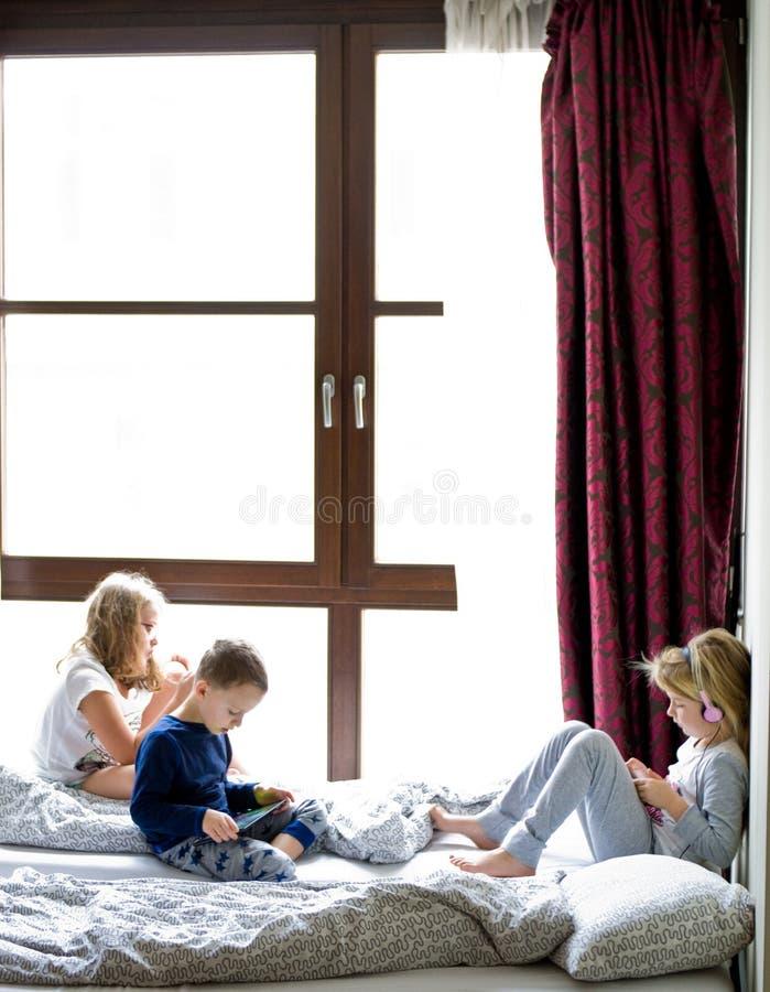 Crianças que jogam na cama com seus tabuletas e telefones fotografia de stock royalty free