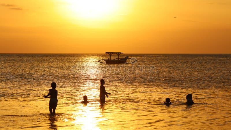 Crianças que jogam na praia com o barco do pescador em Bali, Indonésia durante o por do sol na praia imagem de stock