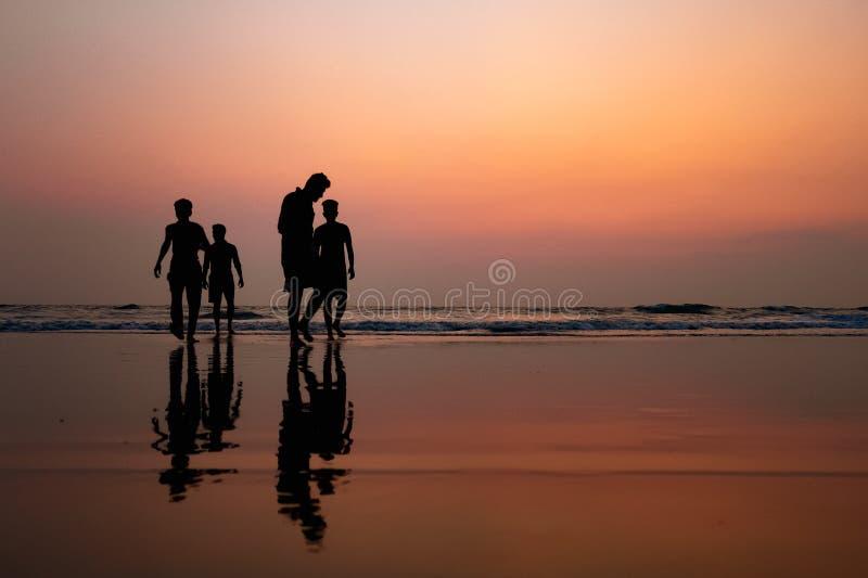 Crianças que jogam na praia durante o por do sol e a reflexão na água fotografia de stock royalty free