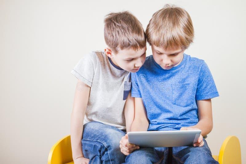 Crianças que jogam na tabuleta Crianças que olham o computador imagens de stock