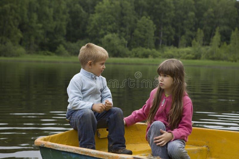Crianças que jogam no catamarã amarelo fotografia de stock