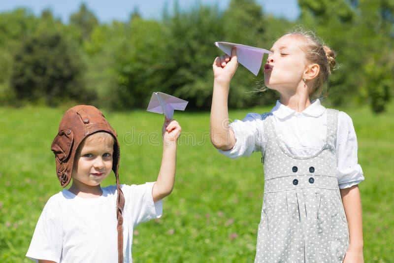 Crianças que jogam nos aviões de papel do parque foto de stock royalty free
