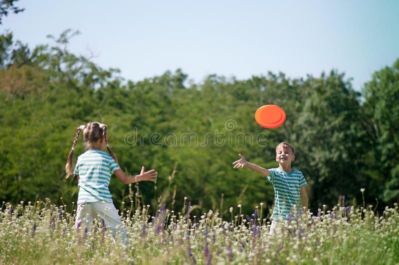 Crianças que jogam o frisbee foto de stock