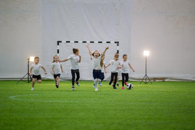 Crianças que jogam o futebol dentro Corredor da equipe de futebol das crianças no campo fotografia de stock