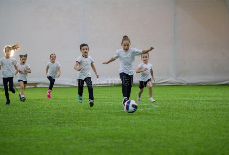 Crianças que jogam o futebol dentro Equipe de futebol das crianças que joga no campo imagens de stock royalty free