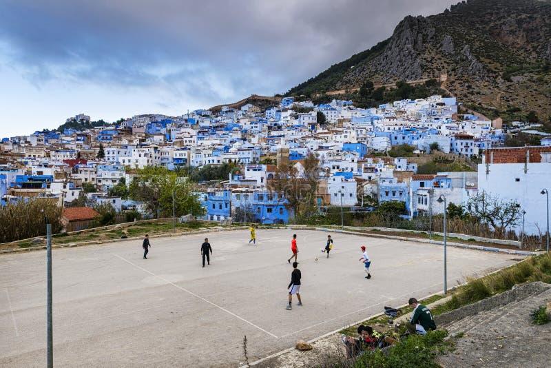 Crianças que jogam o futebol na cidade de Chefchaouen em Marrocos fotografia de stock