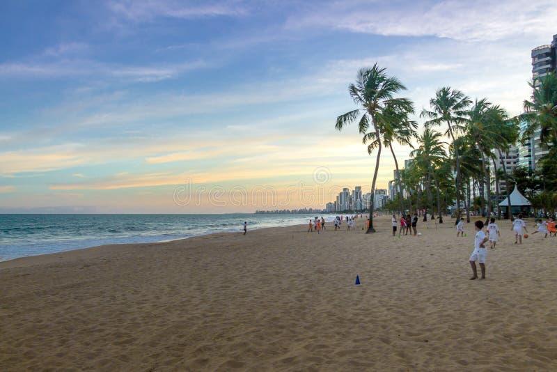 Crianças que jogam o futebol na praia do viagem da boa no por do sol - Recife, Pernambuco, Brasil fotografia de stock