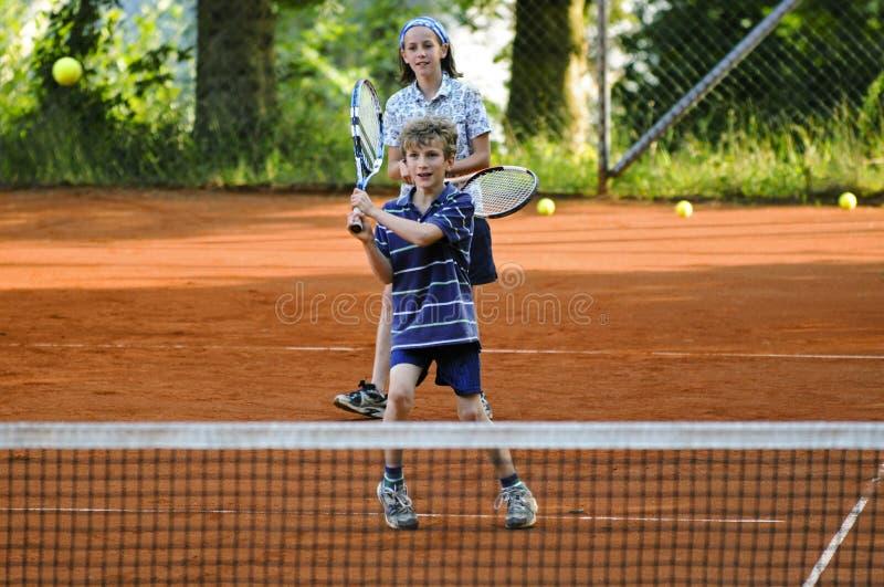 Crianças que jogam o jogo do tênis fotografia de stock