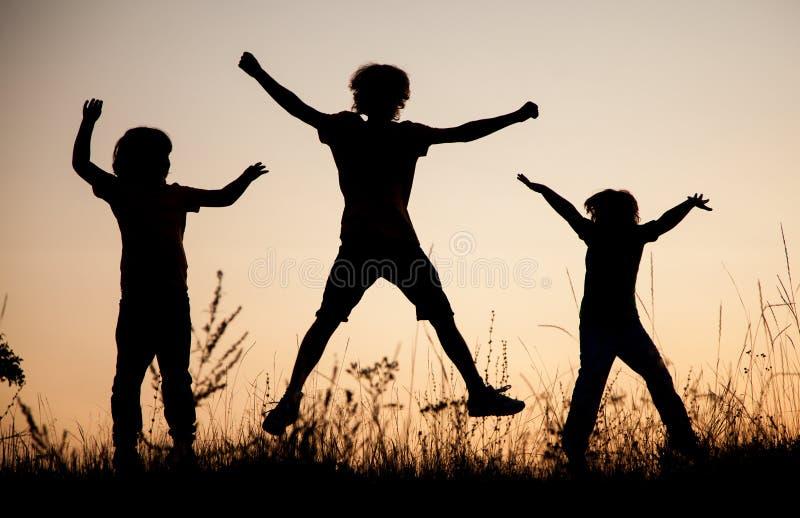Crianças que jogam o salto no prado do por do sol do verão mostrado em silhueta imagens de stock