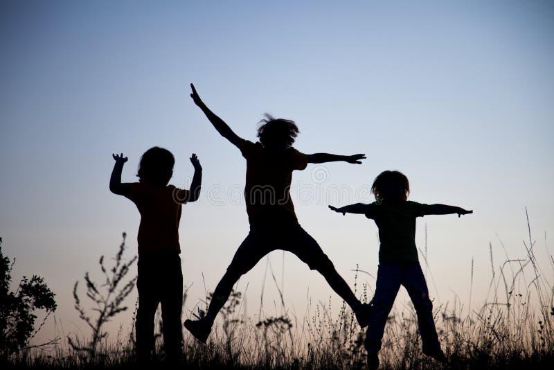 Crianças que jogam o salto no prado do por do sol do verão mostrado em silhueta imagem de stock royalty free
