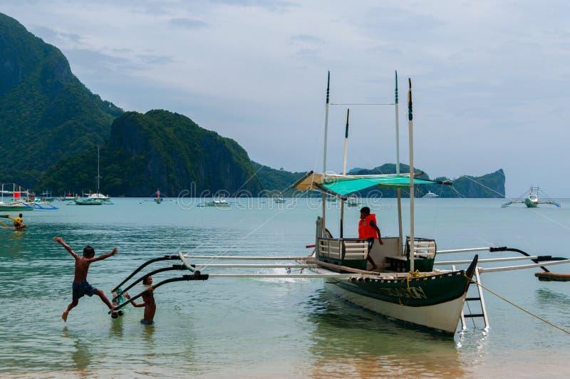 Crianças que jogam pelo barco no litoral imagens de stock