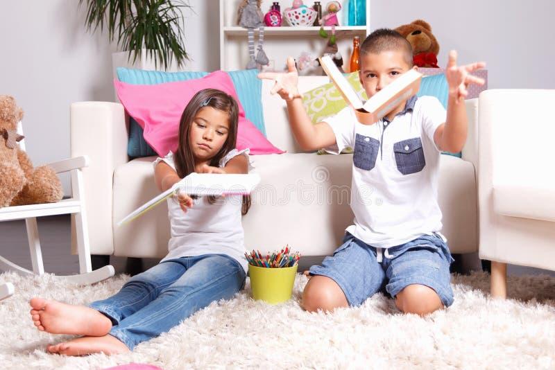 Crianças que jogam seus livros afastado fotografia de stock royalty free